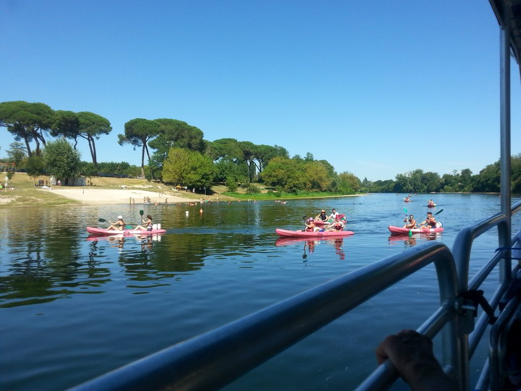 Swimmers and canoers of all ages enjoy the freshness of the Dordogne on a hot day.
